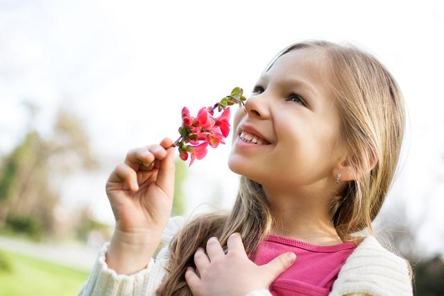 Menina cheirando flor
