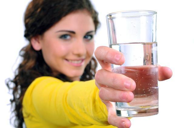 Imagem de mulher segurando copo com água