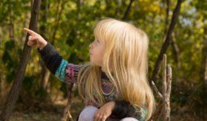 Little blond girl sitting on the ground in the garden pointing to the side and looking in the same direction