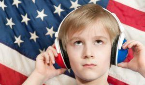 Young boy with headphones standing before a USA flag
