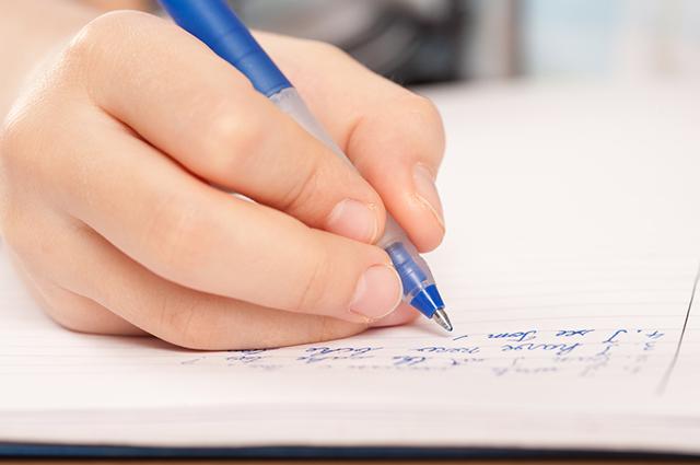 Mão segurando caneta e escrevendo