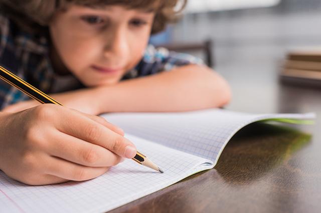 Menino escrevendo no caderno