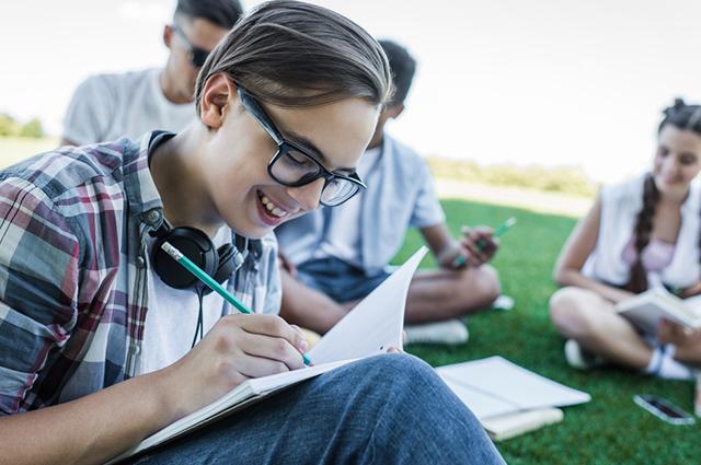 Menino escrevendo texto em caderno