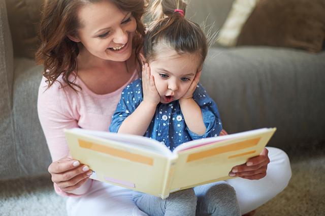 Mãe lendo livro para filhinha