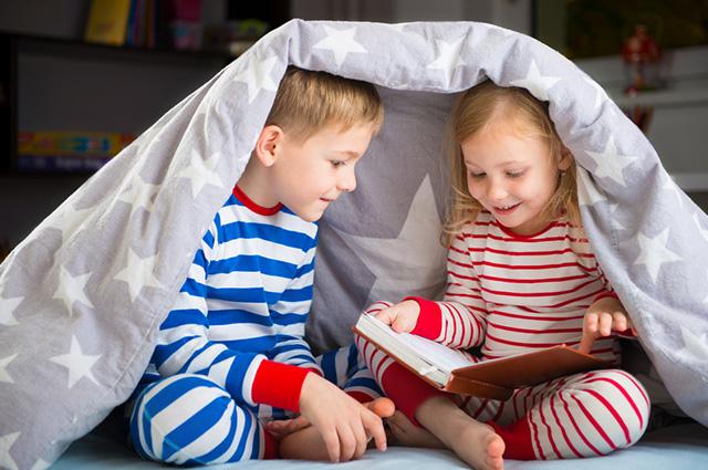Um menino e uma menina lendo livro embaixo de edredon