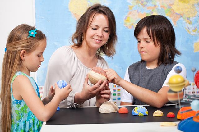 Mãe e dois filhos fazendo uma maquete do sistema solar