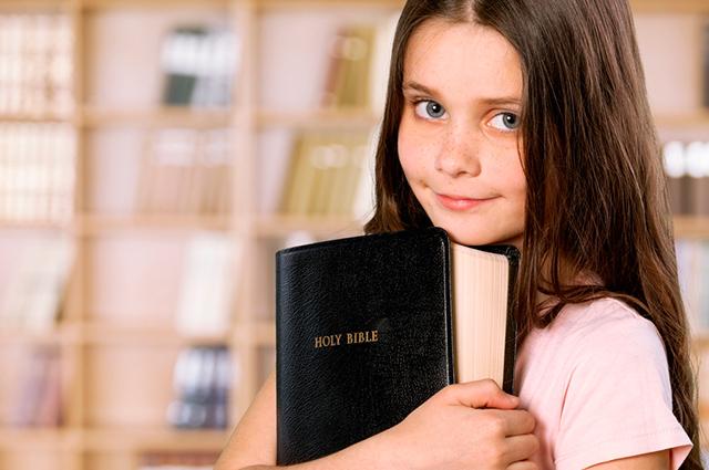 Menina abraçando Bíblia fechada