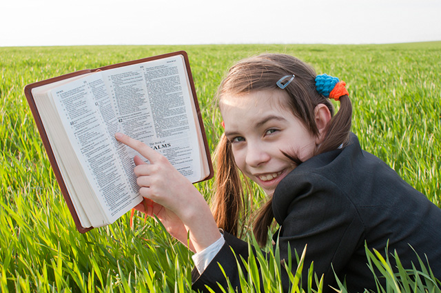 Menina com bíblia na mão sorrindo