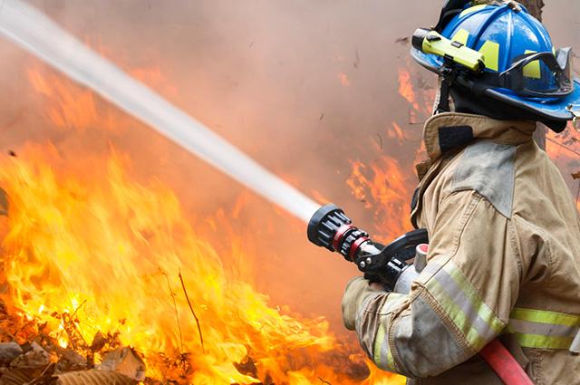 Bombeiro com mangueira apagando chamas