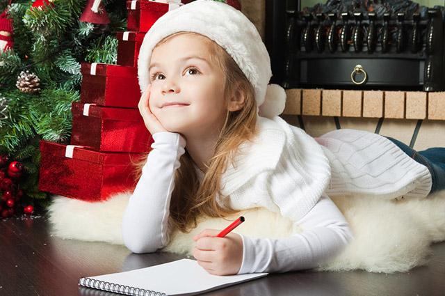 Menina deitado no chão escrevendo carta para Papai Noel
