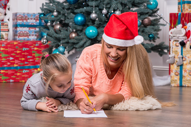 Mãe e filha deitadas no chão escrevendo carta
