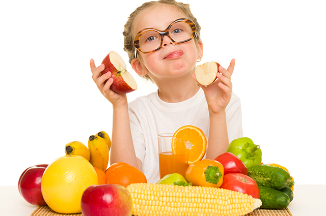 Menina provando frutas diversas